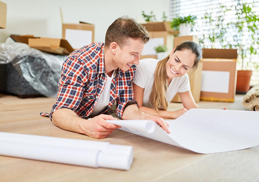 Glückliches junges Paar bei der Planung von Hausbau oder Hauskauf mit Bauplan